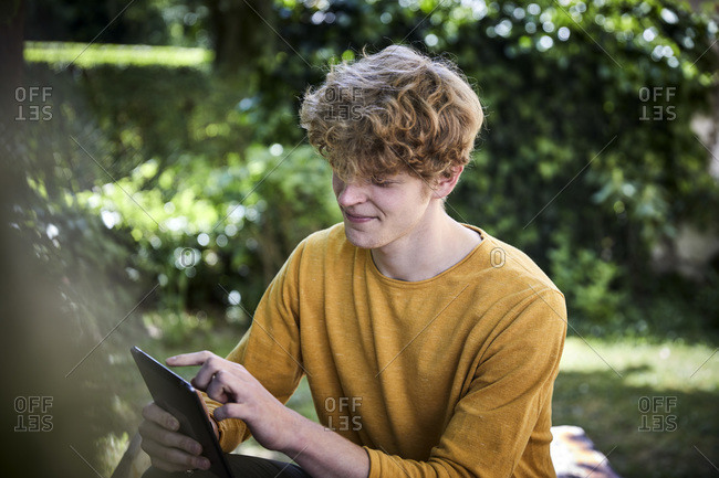 Young man sitting using digital tablet in garden