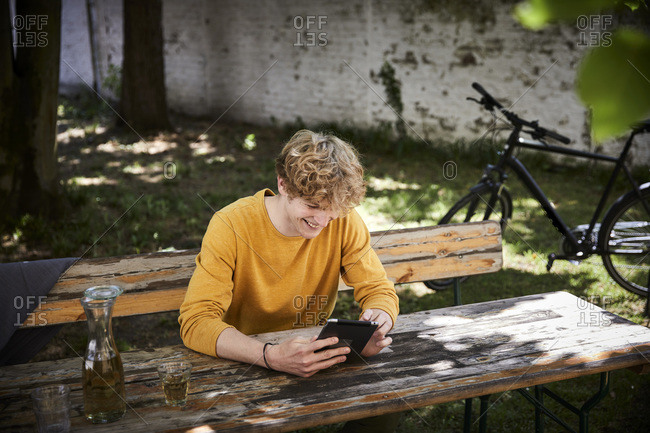 Laughing young man sitting at beer table in garden using digital tablet