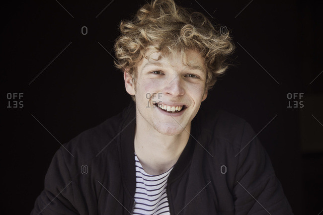 Portrait of laughing young man with curly blond hair against black background