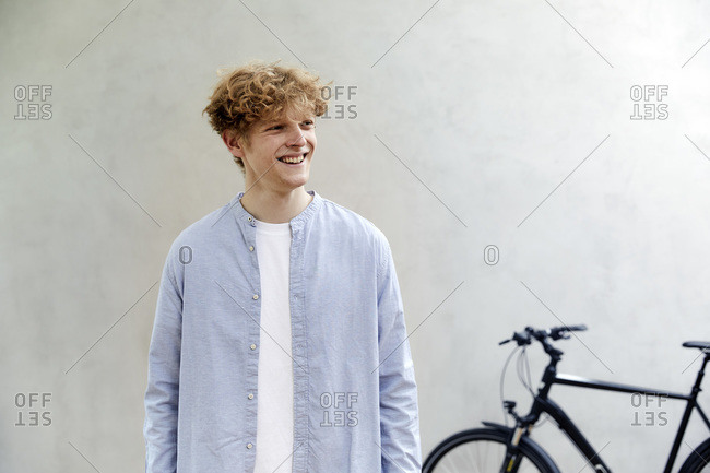 Portrait of smiling young man with curly blond hair standing in front of grey wall