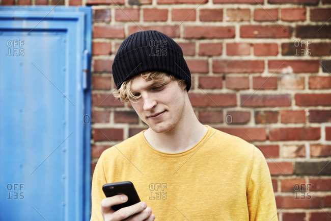 Portrait of young man wearing cap looking at smartphone in front of brick wall