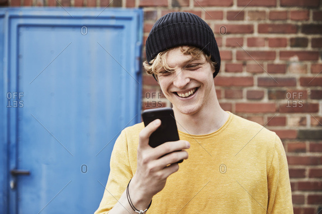Portrait of happy young man wearing cap looking at smartphone in front of brick wall