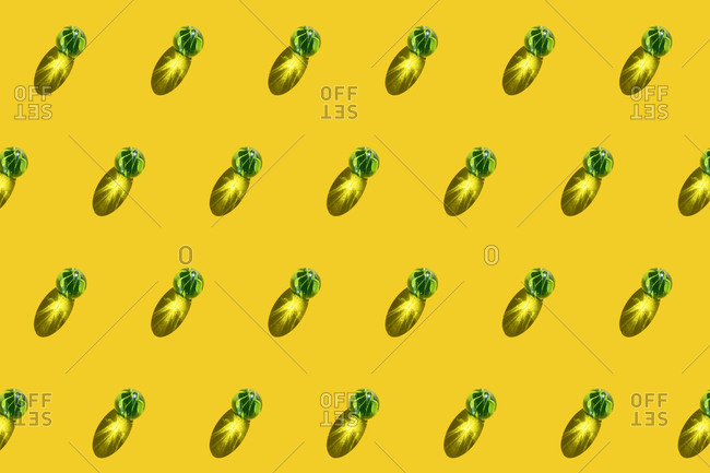 Pattern of green marbles against yellow background