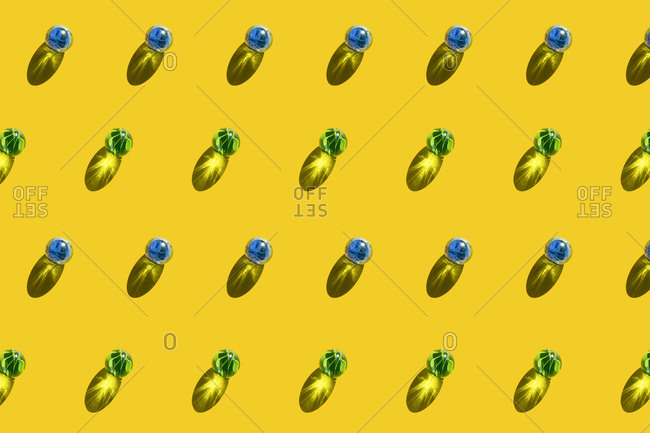 Pattern of blue and green marbles against yellow background