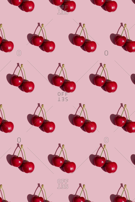 Pattern of fresh cherries on pink background