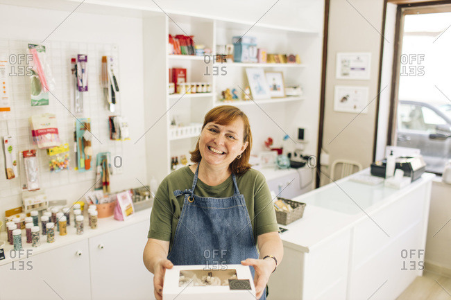 Smiling female baker delivering cupcake box while standing in store