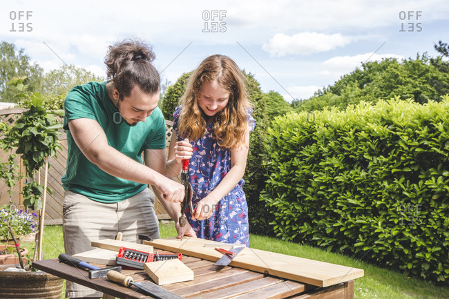 Young man helping sister in carpentry while standing at yard