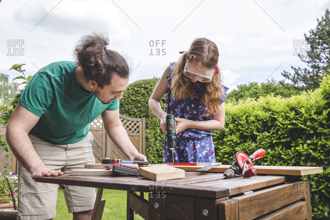 Young man looking at sister drilling on plank while standing in yard