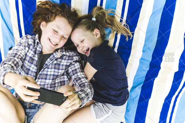 Happy girls sharing smart phone while lying on picnic blanket