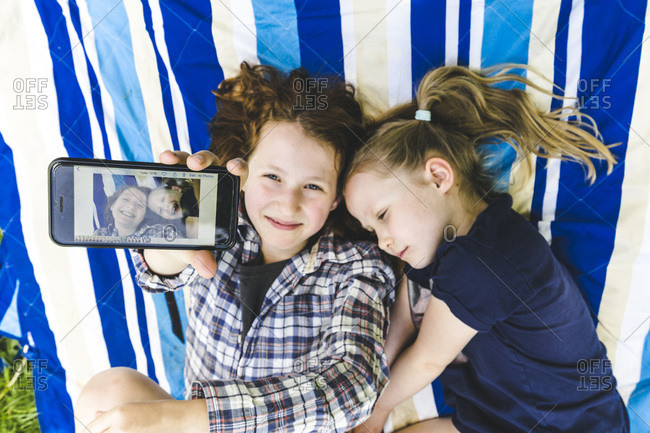 Girl showing photograph on smart phone while lying by sister on picnic blanket