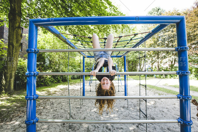 Smiling girl hanging upside down on jungle gym in playground at park