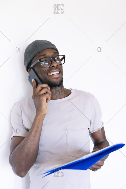 Smiling young businessman holding file and talking on smart phone while looking away against white background