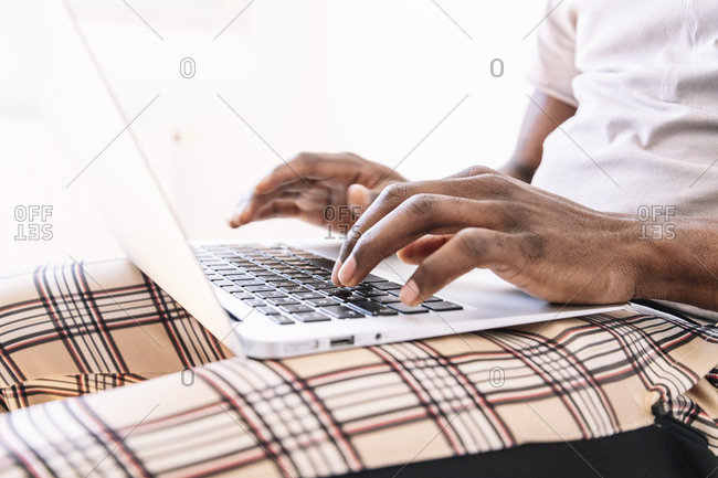 Young businessman typing on laptop while working at home