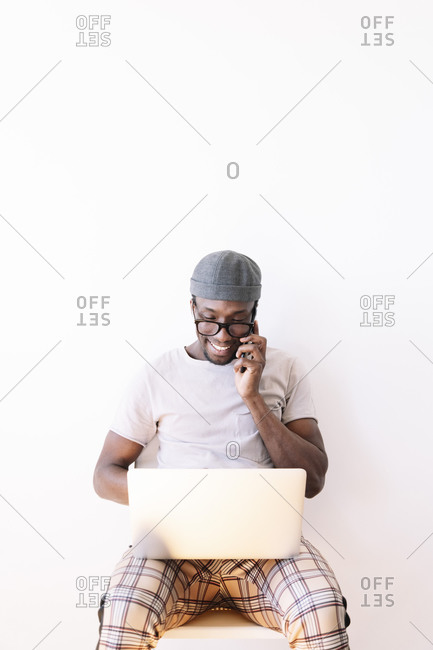 Smiling young man talking on mobile phone while using laptop against white background