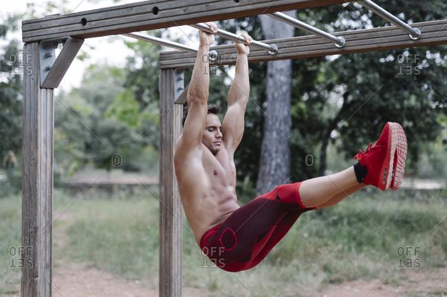 Man lifting leg hanging on jungle gym