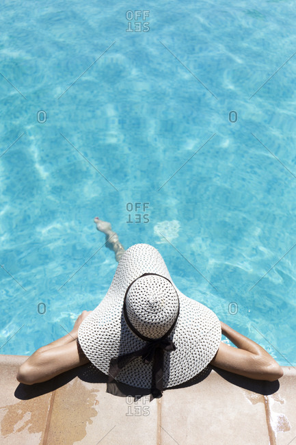 Young woman wearing hat relaxing in swimming pool at tourist resort during sunny day