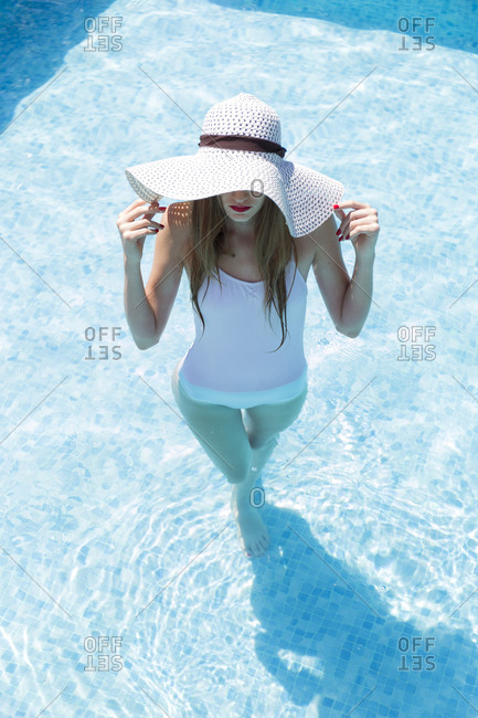Young woman wearing hat swimming in pool at tourist resort during sunny day