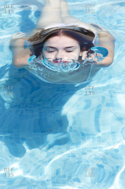Close-up of young woman wearing eyes closed swimming in pool at tourist resort