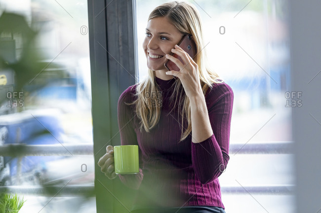Smiling female entrepreneur talking over smart phone while sitting against window in office