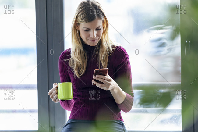 Businesswoman holding coffee mug using smart phone while sitting in office
