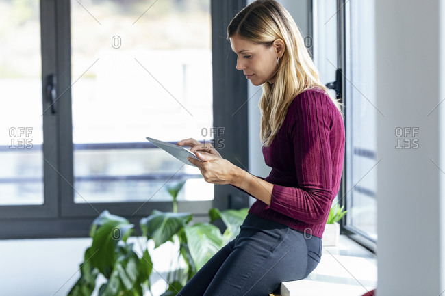 Female entrepreneur using digital tablet while leaning on table in office