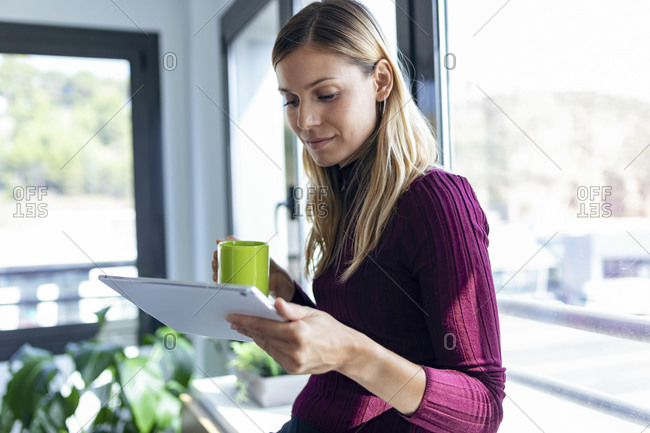 Businesswoman holding coffee mug using digital tablet in office