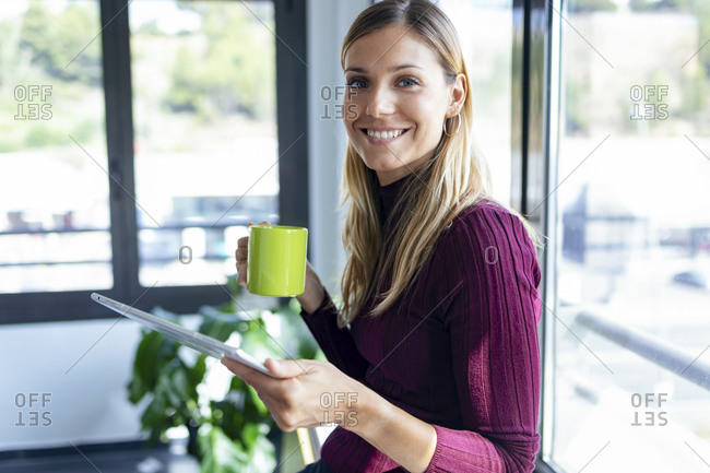 Smiling businesswoman holding coffee mug using digital tablet in office