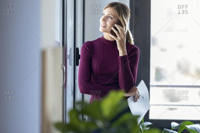 Entrepreneur talking over smart phone while standing by window in office