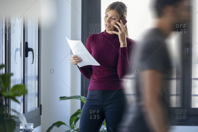 Businesswoman talking over smart phone while male coworker walking in office