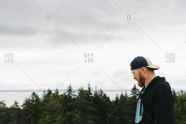 Bearded handsome man wearing cap at Bay of Fundy against sky