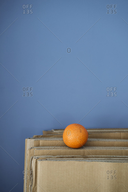 Single orange on cardboard against blue wall