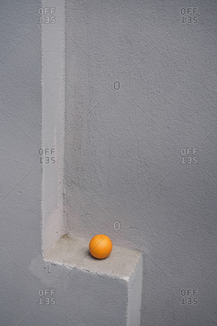 Single orange on a gray wall spur
