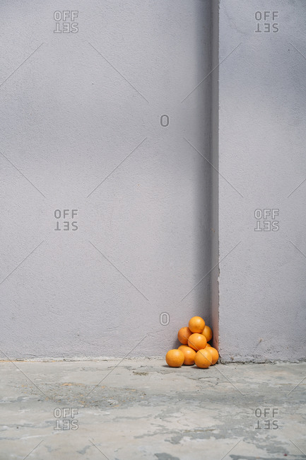 Pile of oranges in corner of a gray wall