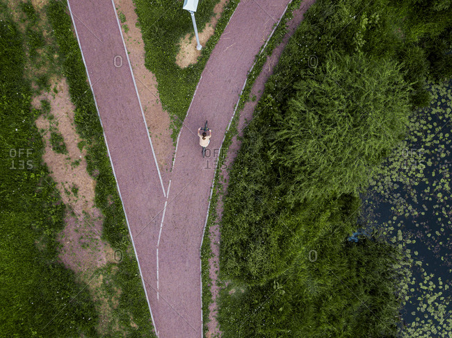 Russia- Leningrad Oblast- Tikhvin- Aerial view of female cyclist riding along lakeshore footpath in park