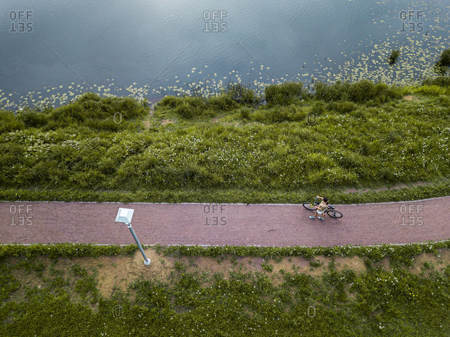 Russia- Leningrad Oblast- Tikhvin- Aerial view of female cyclist taking break on lakeshore footpath in park