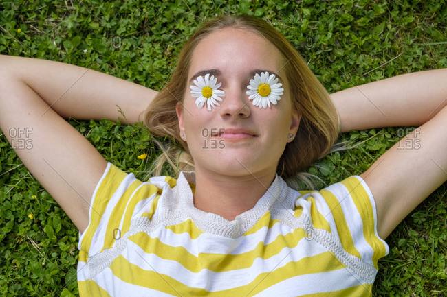 Close-up of young woman with daisies on eyes lying over grassy land in park