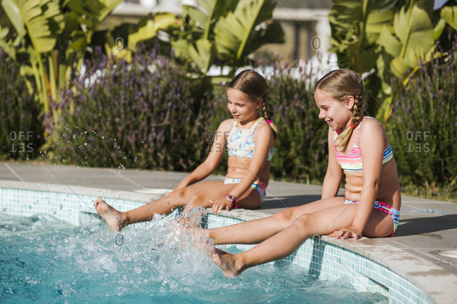Cheerful sisters splashing water in swimming pool on sunny day