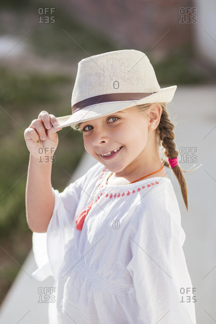 Smiling cute girl wearing hat and white sundress on summer day