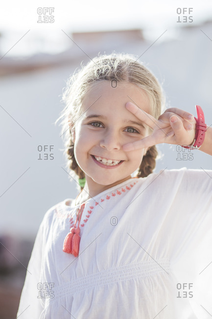 Smiling cute girl showing peace sign while standing outdoors on sunny day