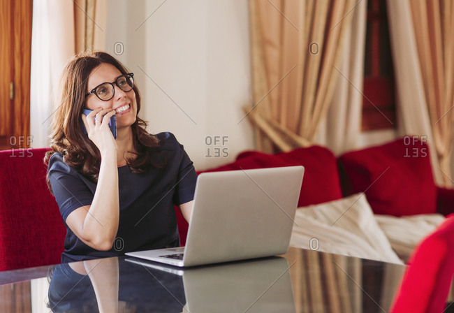 Smiling businesswoman talking on mobile phone while sitting with laptop at table in living room