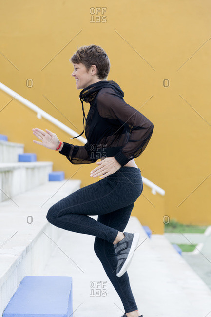 Smiling athletic woman running on stairs