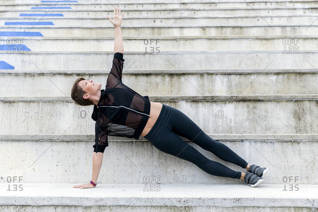 Athletic woman during workout on stairs- side plank