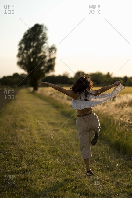 Woman dancing at field in the evening
