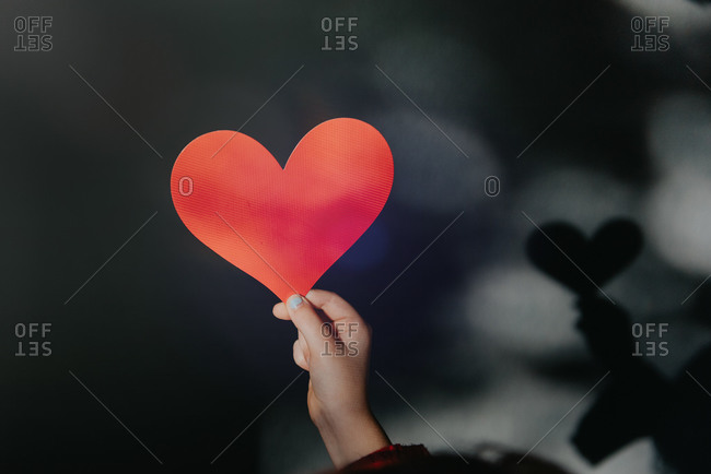 Hand holding paper heart with shadow