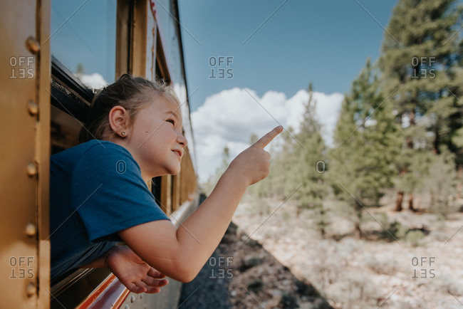 Young girl pointing out a train window