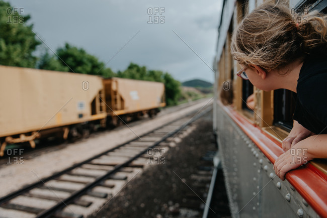 Young blonde girl with head out train window