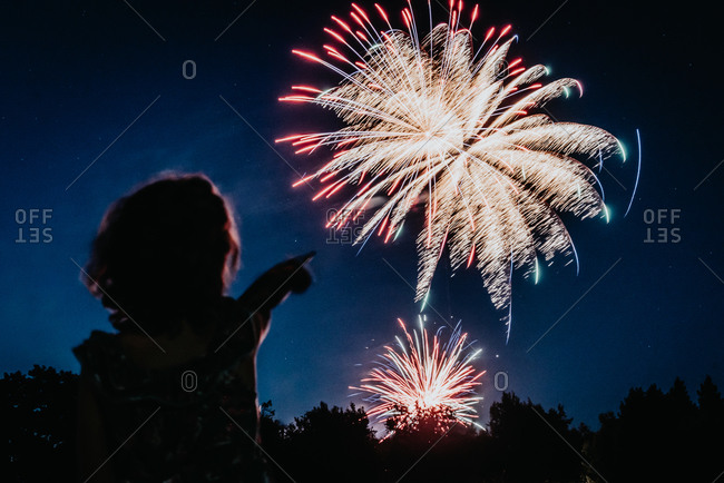 Young girl pointing at fireworks