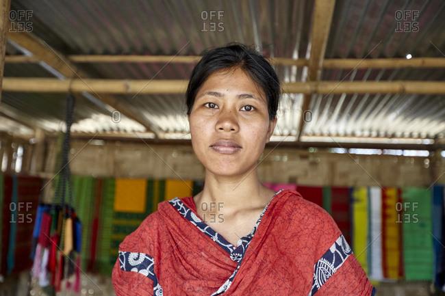 Dulochora Village, Sreemangal, Bangladesh - April 30, 2013: A Tripura woman working in a shop selling colorful handmade textiles