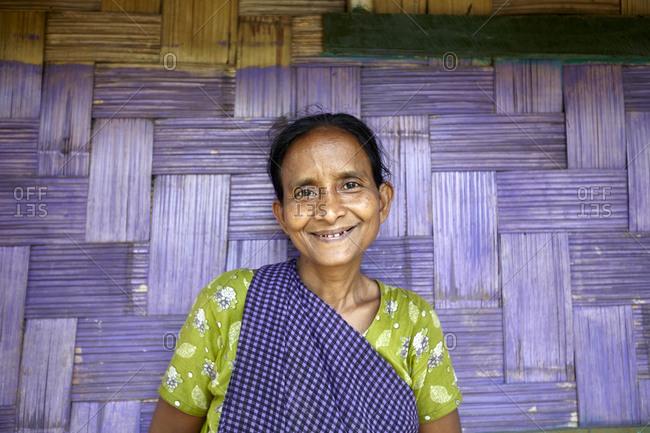 Nirala Para village, Bangladesh - May 1, 2013: Portrait of a Khasi woman in front of a purple wall