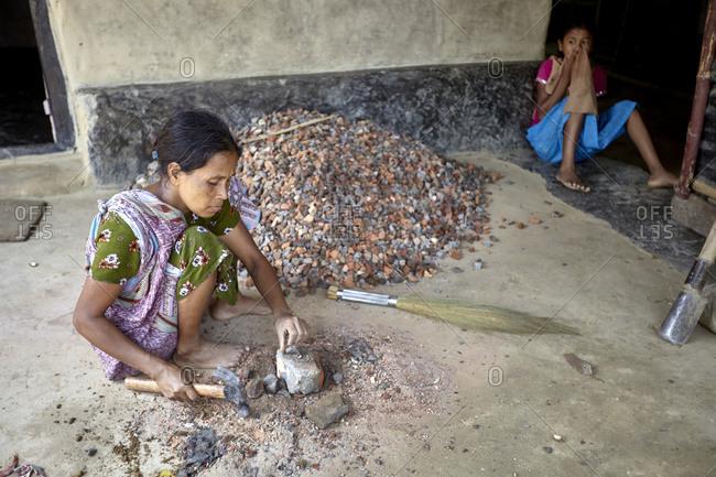 Nirala Para village, Bangladesh - May 1, 2013: A Khasi woman breaking a brick with a hammer